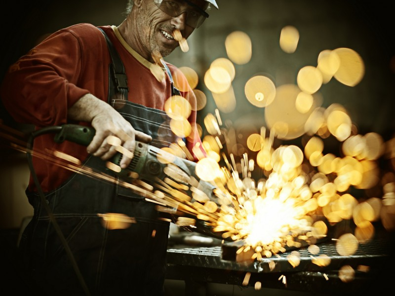 Industrial worker cutting and welding metal with many sharp spar
